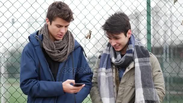 Discuter avec des inconnus ou leur sourire dans la rue ou ailleurs fait le plus grand bien ! Depositphotos_176997514-stock-video-two-young-men-reading-text