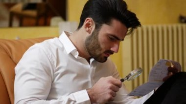 Young Man Examining Contract or Bill with Magnifying Glass
