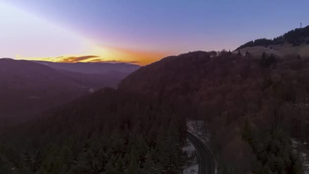 Západ slunce nad silnici přes podzimní les