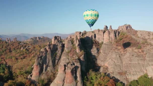 Amazing panoramic video with hot air balloon flying over picturesque rock formation lit by the morning autumn sun, Belogradchik rocks, Bulgaria