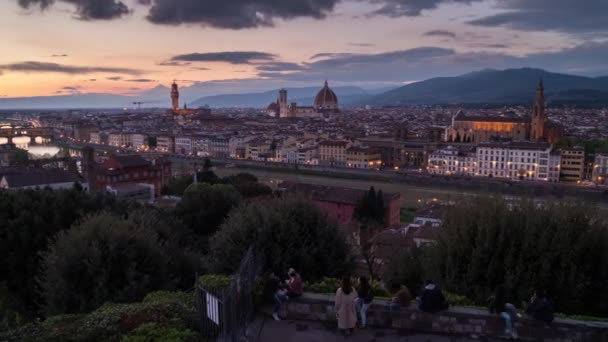 Florence, Italy - April 6, 2019: Amazing sunset view of Florence city, Italy with the river Arno, Ponte Vecchio, Palazzo Vecchio and Cathedral of Santa Maria del Fiore (Duomo). Panoramic time lapse from day to night.