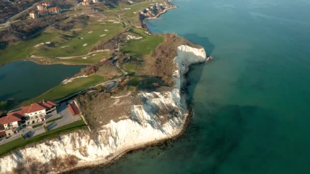 Panoramic video of picturesque landscape with green hills, golf fields and buildings near the rocky coastline of the Black sea, Thracian Cliffs golf and beach resort, Bulgaria.