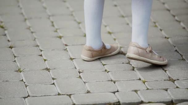 Dívka v béžových sandálech ustoupí, žena v černých sandálech se blíží k dětským nohám