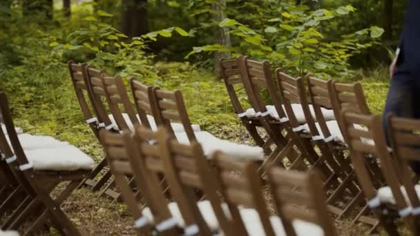 Wooden chairs prepared for wedding ceremony in forest, a man in suit is walking