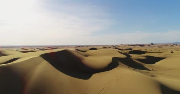 Letecký pohled na letící nad písečnými dunami v poušti při západu slunce