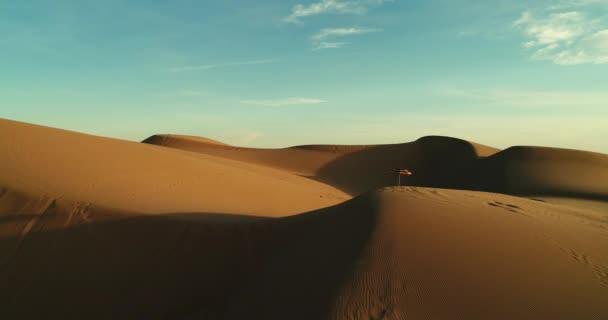 Letecký létat v barevné slunečníky izolován v písečných dunách při západu slunce