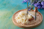 Fotografie French cheese Monk Head sliced with clove petals on a wooden round surface. Bouquet of lavender.