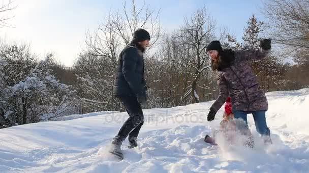 Šťastná rodina baví hraní na sněhu v zasněženém parku.
