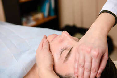 Doctor massages the face to the patient