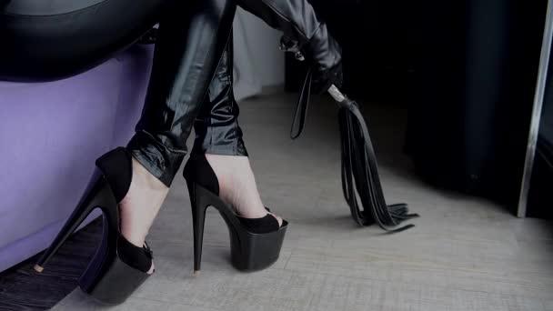 Žena na vysokých podpatcích přesunout bič na podlaze