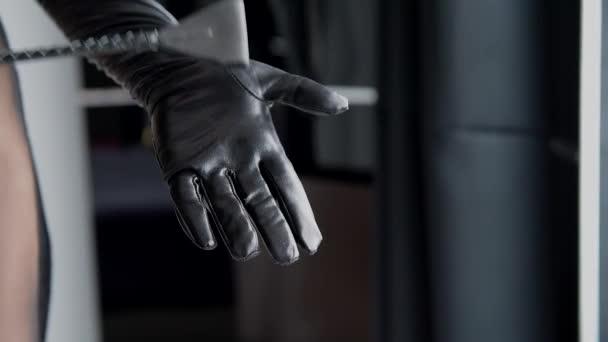 Žena narazila ruku v černé kožené rukavice s zásobníku. Žena naplácat jí ruku dlaní s Oříznout bič