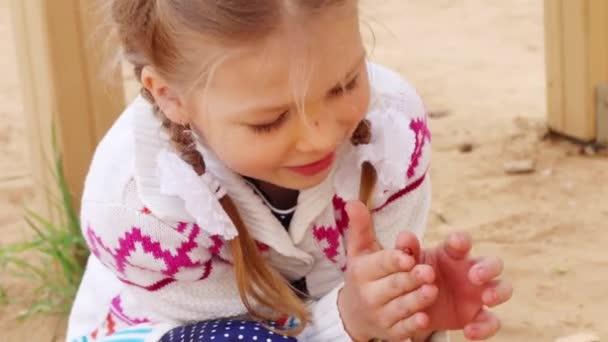 Gilr felice gioca con brillante coccinella che si siede sulla barretta allaperto, primo piano