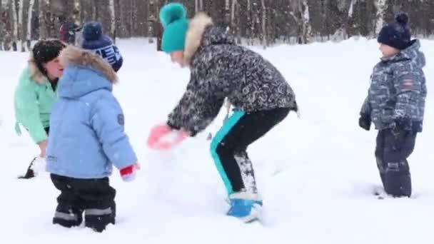 Nő és három gyermek hányni hó alatt havazás Park