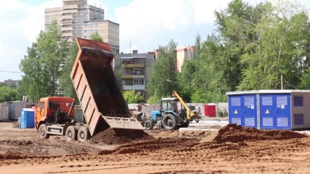 Nákladní a traktory práce na staveništi v letní den, video se zvukem