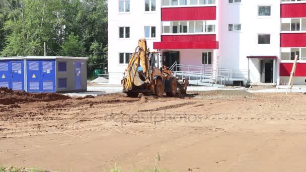 Žlutý traktor funguje na staveništi v letním dni