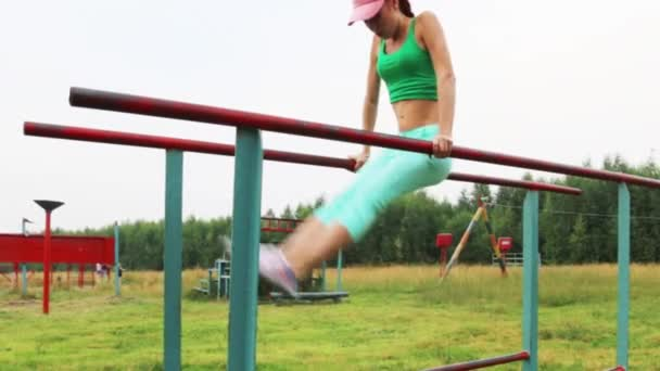 Girl does exercise on parallel bars at summer evening outdoor