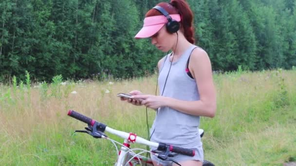 Woman in cap with bicycle listens to music at summer outdoor