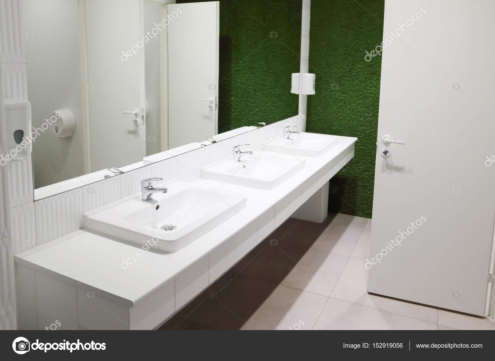 Bianchi tre lavandini in bagno con grande specchio e parete verde ...
