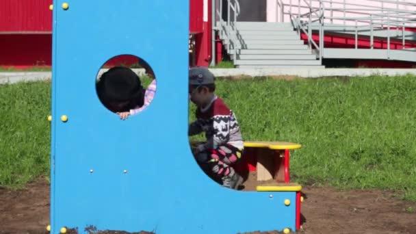 Three happy children play in bright sandbox on playground at sunny day
