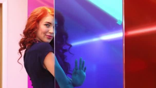 Mladá krásná žena představuje za barevnými skly v pokoji