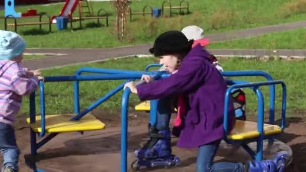 Tři šťastné děti budou hrát na kruhový objezd na slunečný den