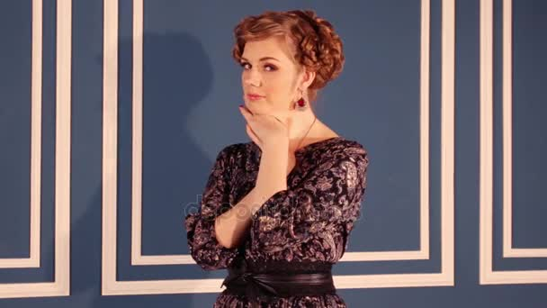 Pretty woman in dress poses near wall in blue room