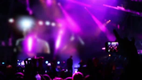 Mano con il telefono cellulare al concerto con spettacolo di laser e