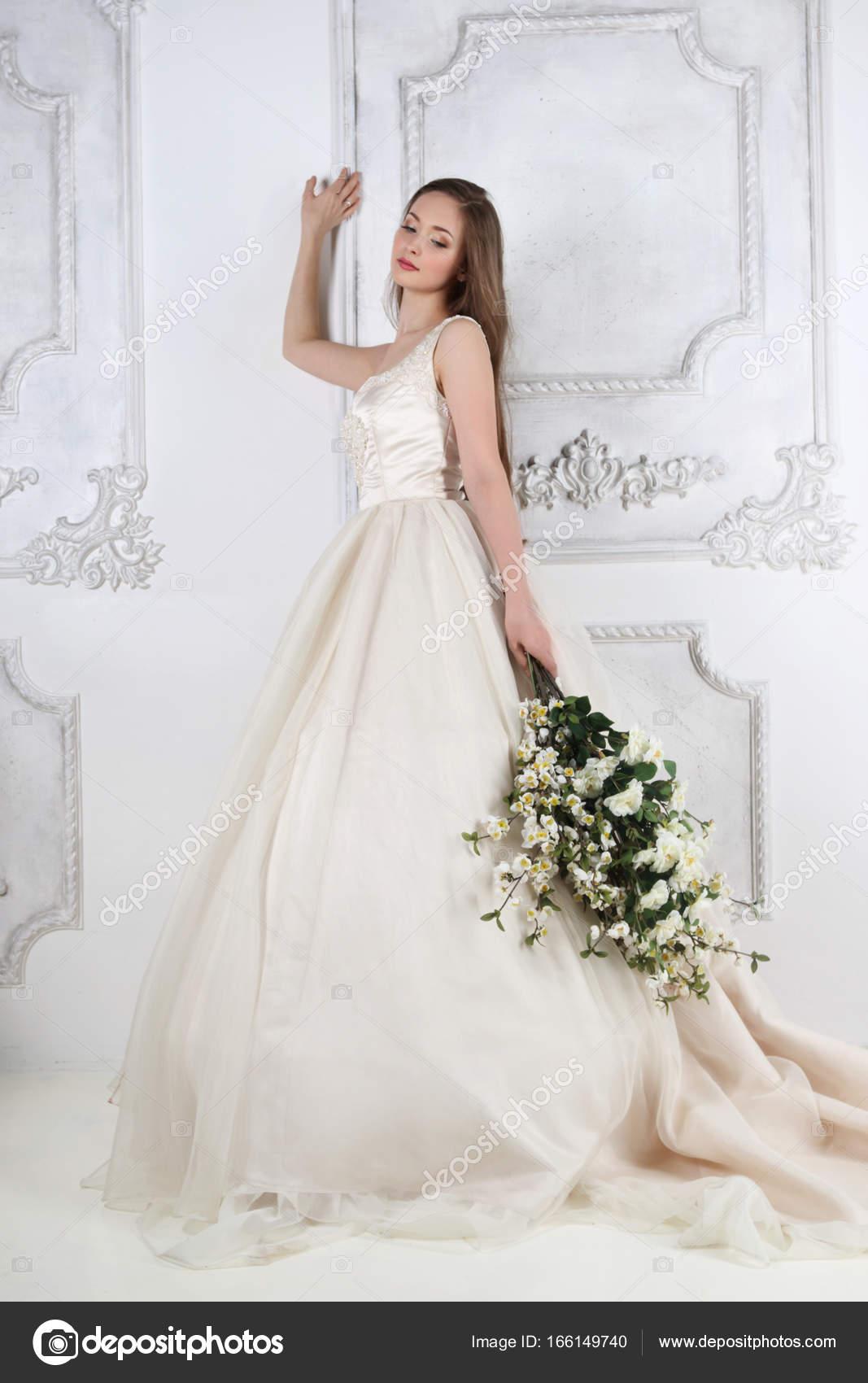 Junge Frau im langen Kleid besitzt weiße Blüten in weißen Studio ne ...