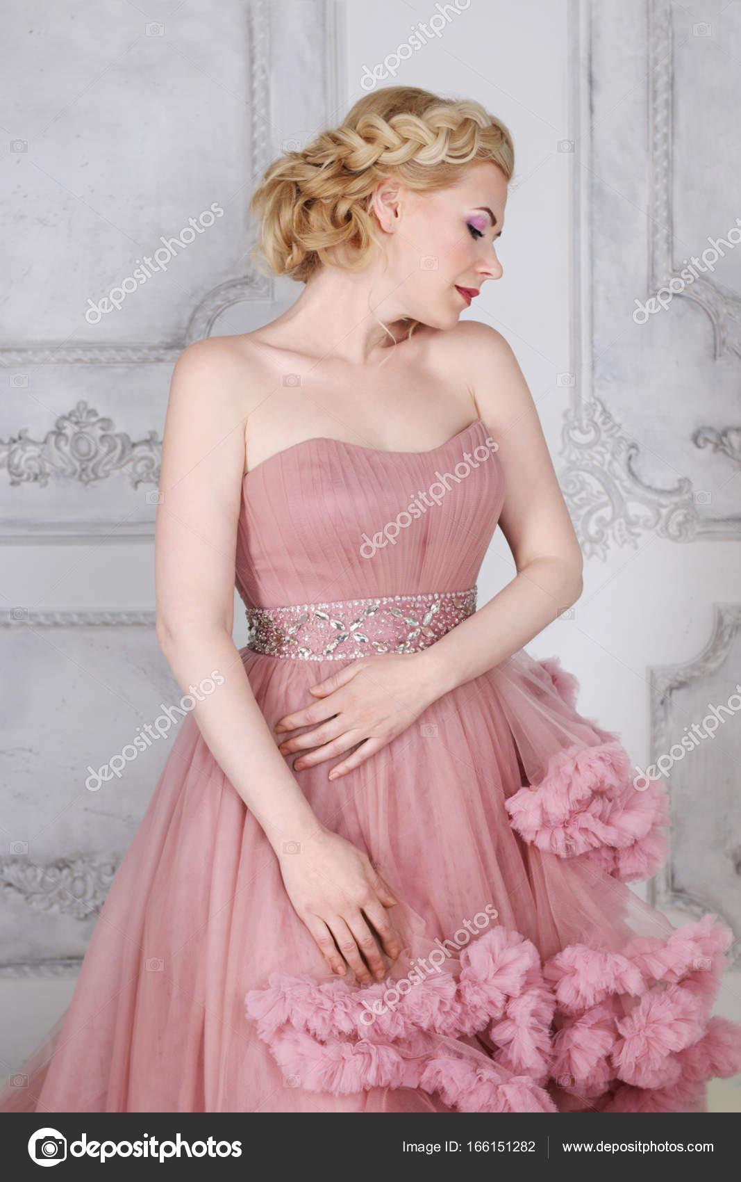 Bonita rubia en vestido hermoso con poses de peinado en espárrago ...
