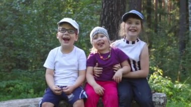 Three children smile, embrace and grimace in summer park