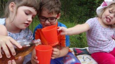 Girl pours lemonade for boy and girl among grass in summer park