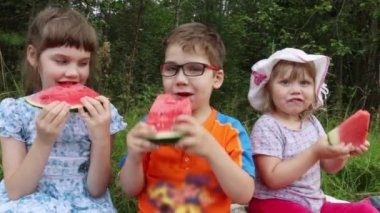 Three happy children eat watermelon in green summer park