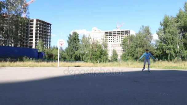 Girl roller skates in yard near buildings under construction at sunny day