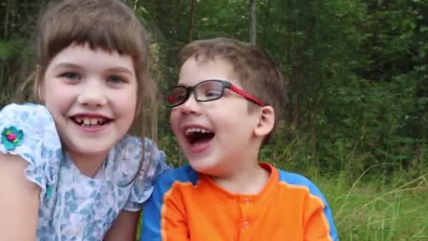 Tři děti smát mezi trávy v létě park, zblízka