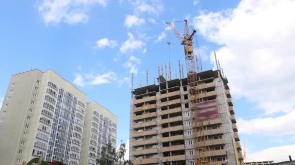 Tall crane works at construction site with residential building at summer