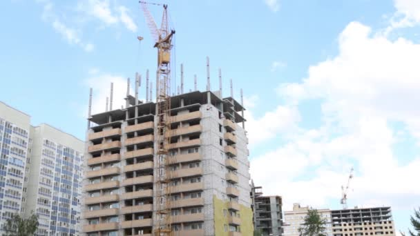 Tall crane works at construction site with residential building, time lapse