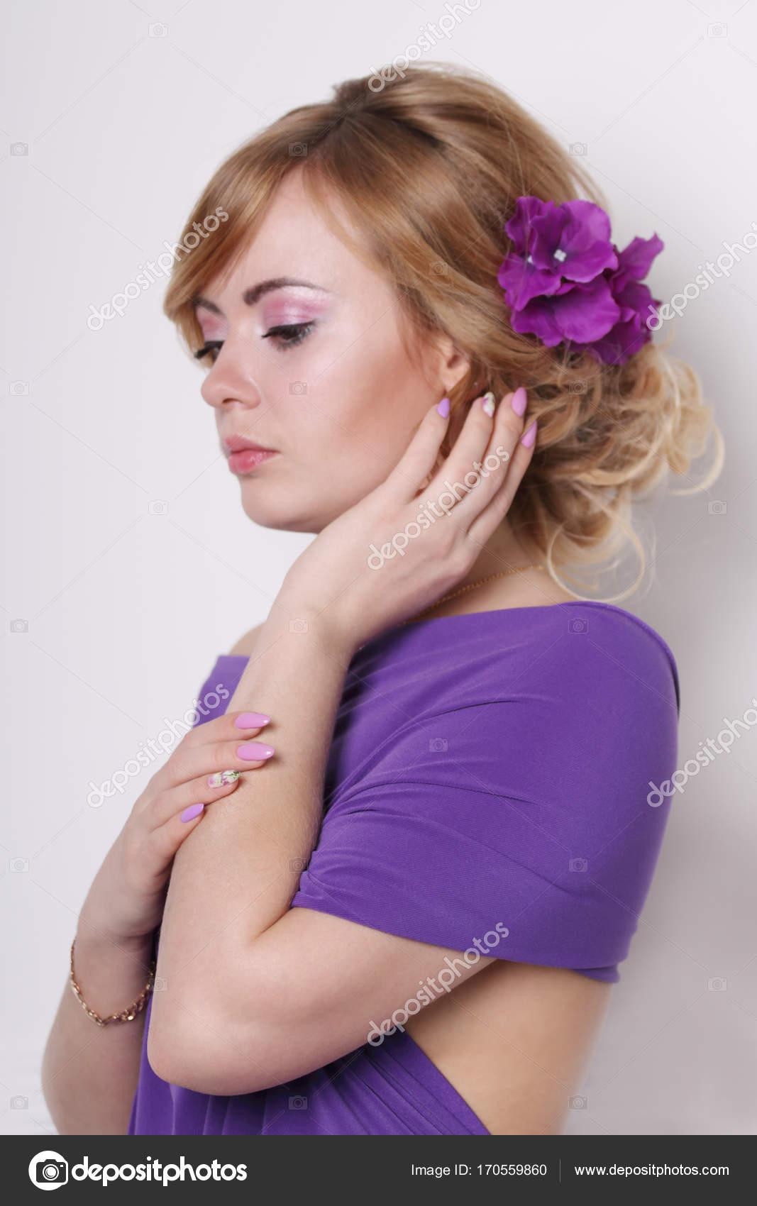 489b0b965455 Όμορφη νεαρή γυναίκα με μωβ φόρεμα με λουλούδια στα μαλλιά της — Φωτογραφία  Αρχείου