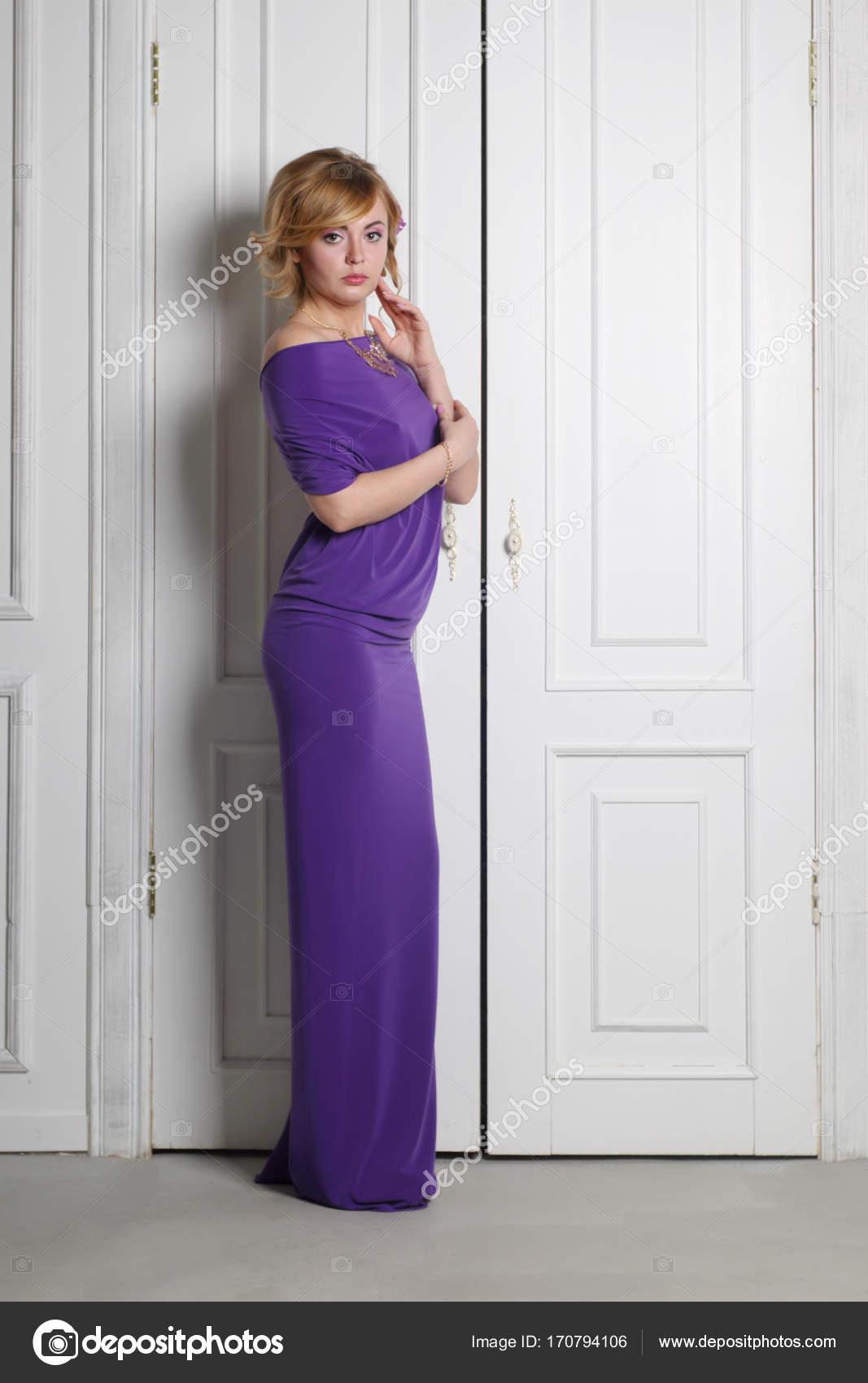 b7ddaf97e9a6 γυναίκα στο μακρύ μωβ φόρεμα με λουλούδι της τρίχας που παρουσιάζουν ...
