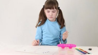 Mosolygó lány kék akvarell festék pillangó tábla fehér szobában