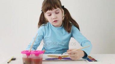 Mosolygó csinos lány festékek akvarell pillangó tábla fehér szobában