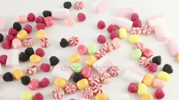 Many bright sweet candies and marshmallows on white table