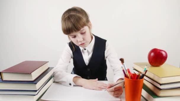 Iskolás asztalnál ül és ír könyveket és apple közelében