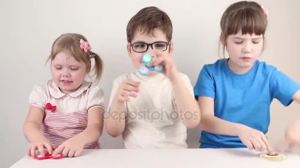 Tři šťastné děti hrát s spirály v bílém studio