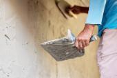 Nahaufnahme der Hand eines Arbeiters, der eine Zementverputzvorrichtung hält, um eine Mauer im Haus auf der Baustelle zu bauen