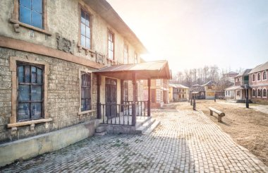 Artificial scenery of an old house with a visor above the entrance on an old city street in Kinogorodok in Leninsky Gorky on a spring sunny day. Caption: Sewing studio