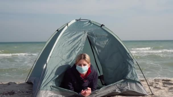 A young woman in a protective mask lies in a tent on the seashore. Isolated place. Escape from the epidemic of coronavirus. The failure of the tourist season.