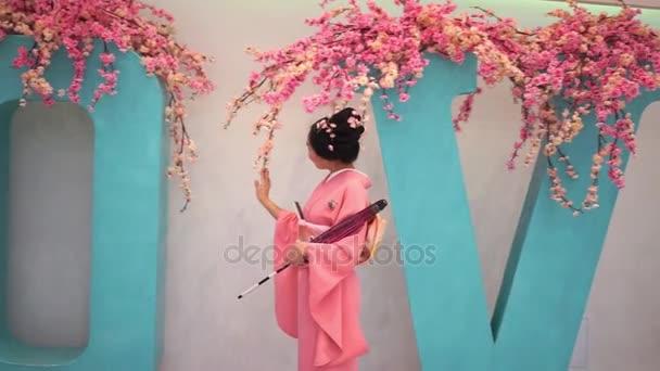 Gejša v růžové kimono s deštníkem, chůze v blízkosti zdi a velkými písmeny s Třešňové květy