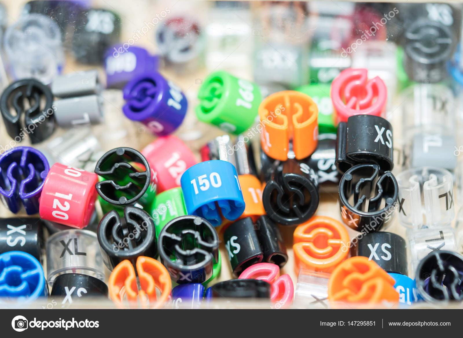 430ad1690aa2 Πλαστικές ετικέτες που υποδηλώνουν το μέγεθος των ρούχων για κρεμάστρες σε  ένα κουτί — Φωτογραφία Αρχείου