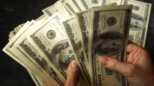 Female hands count United States one hundred dollar bills, periodically gets off the count.