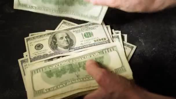 Ženské ruce spočítat Spojené státy sto dolarové bankovky, je obracet na druhou stranu a skládání je na stole.